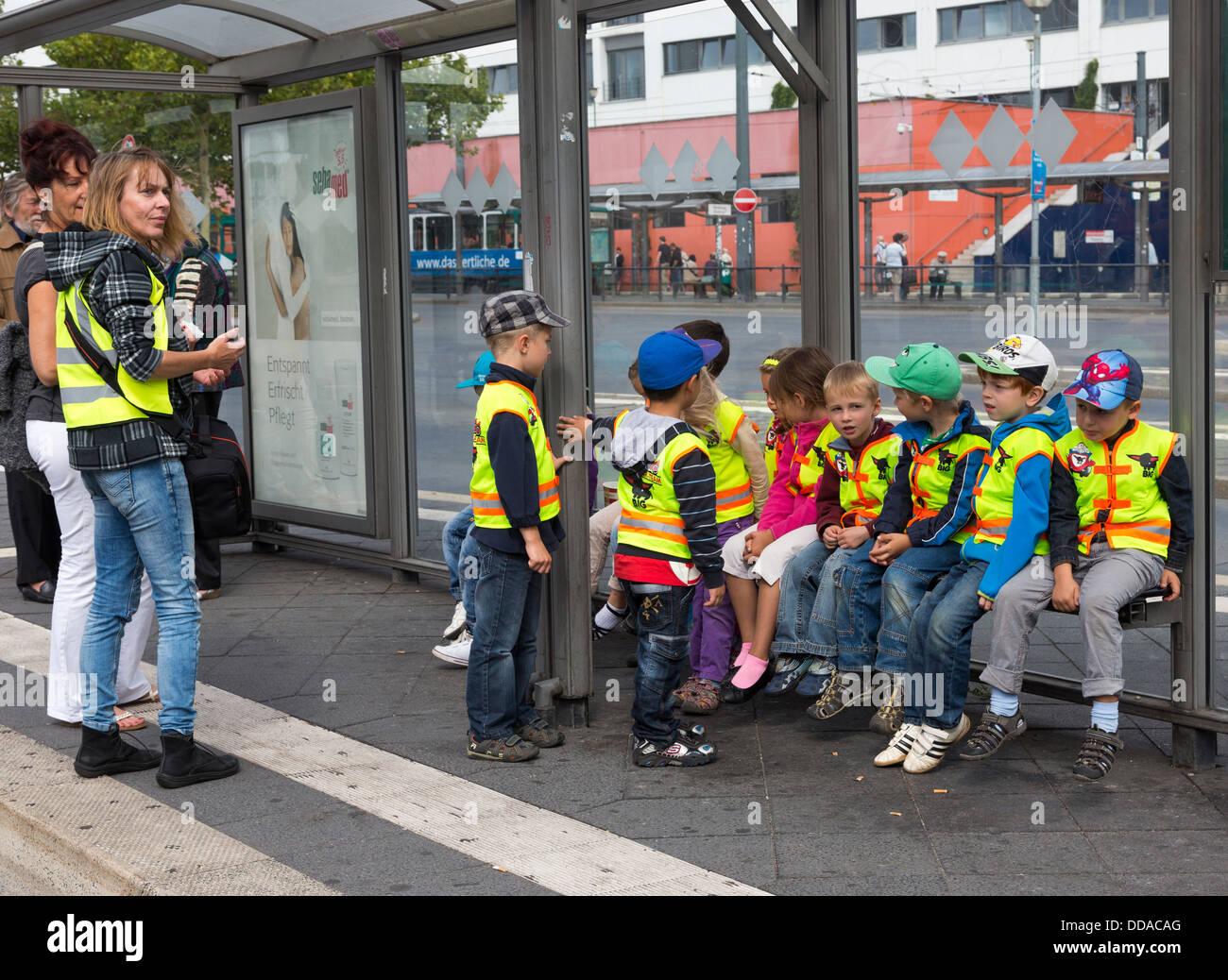 Maestros y Niños en parada de autobús en viaje de campo vistiendo chalecos de seguridad fluorescentes, Imagen De Stock