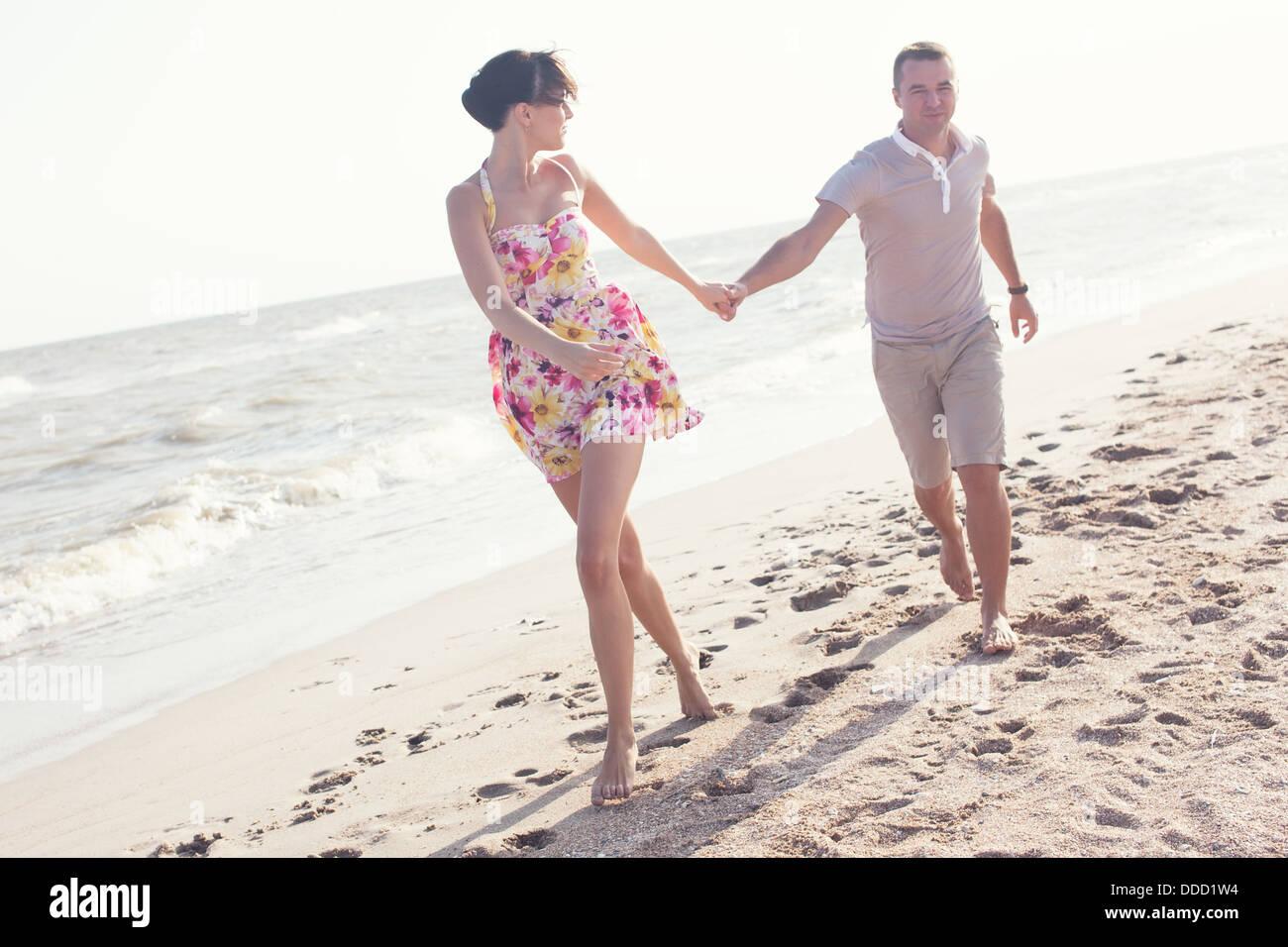 Imagen dinámica de marcha pareja en la playa. Cogidos de la mano. Verano divertido Foto de stock