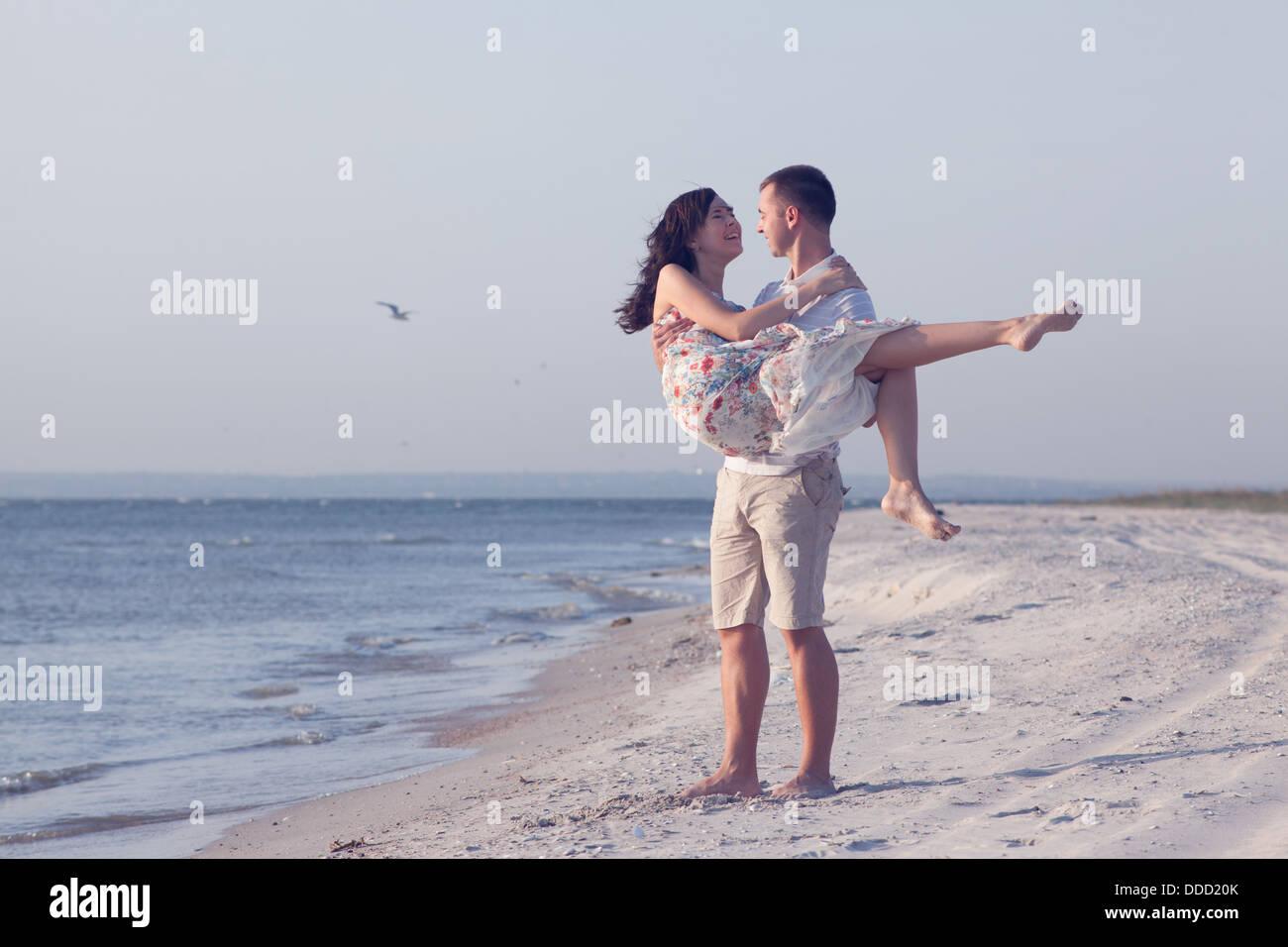 Feliz pareja joven en ropa blanca tienen recreación romántica y diversión en la hermosa playa de vacaciones Foto de stock