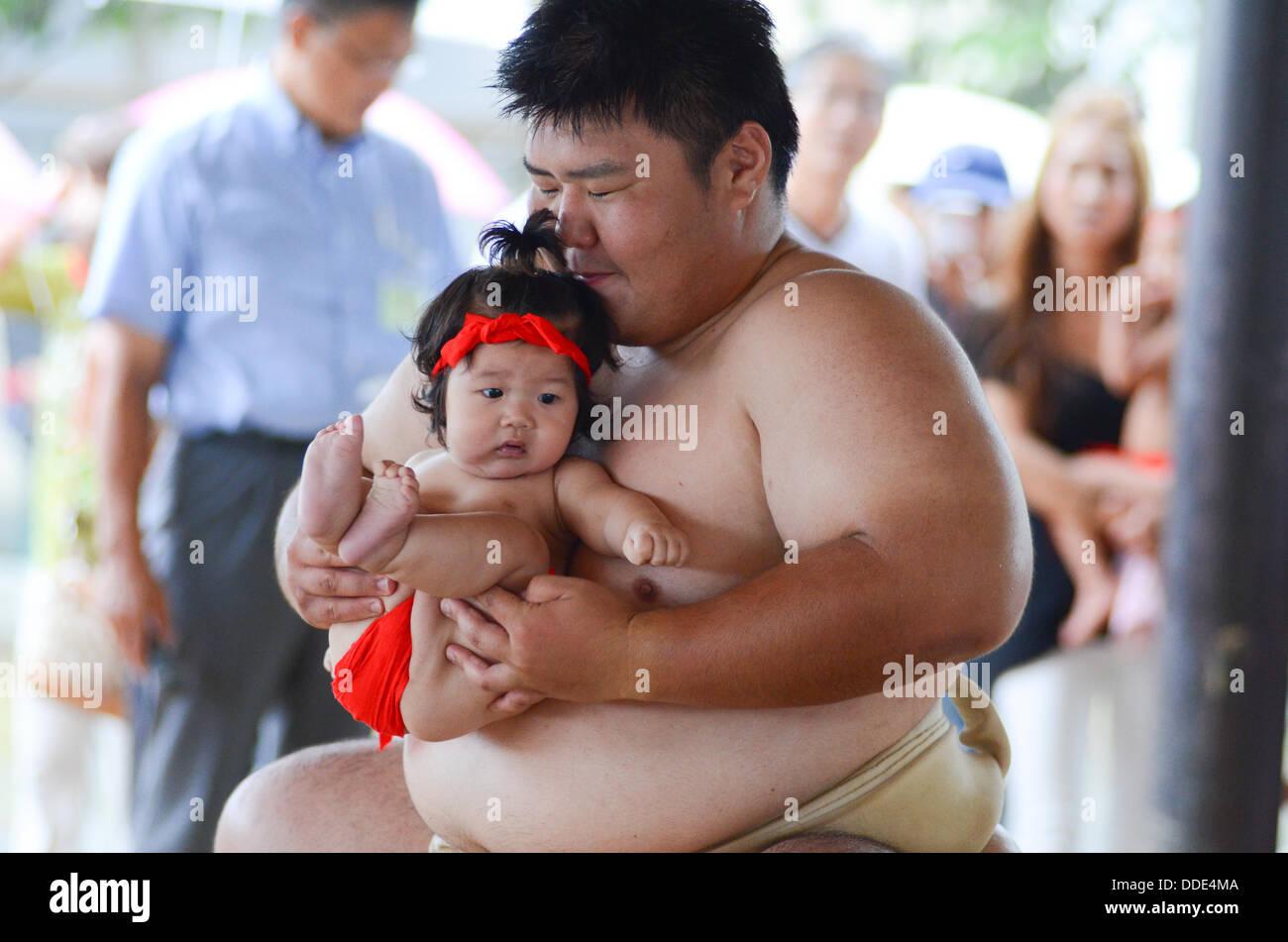 Los luchadores y los bebés toman parte en un evento de sumo en Matsuo Taisha Shrine en Kyoto, Japón. Imagen De Stock