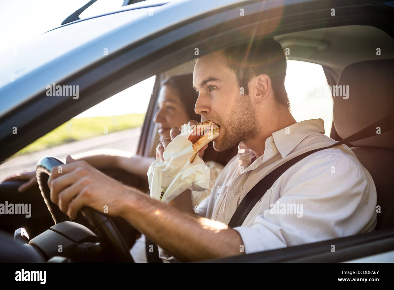 Pareja en coche - el hombre está conduciendo y comer baguette Imagen De Stock