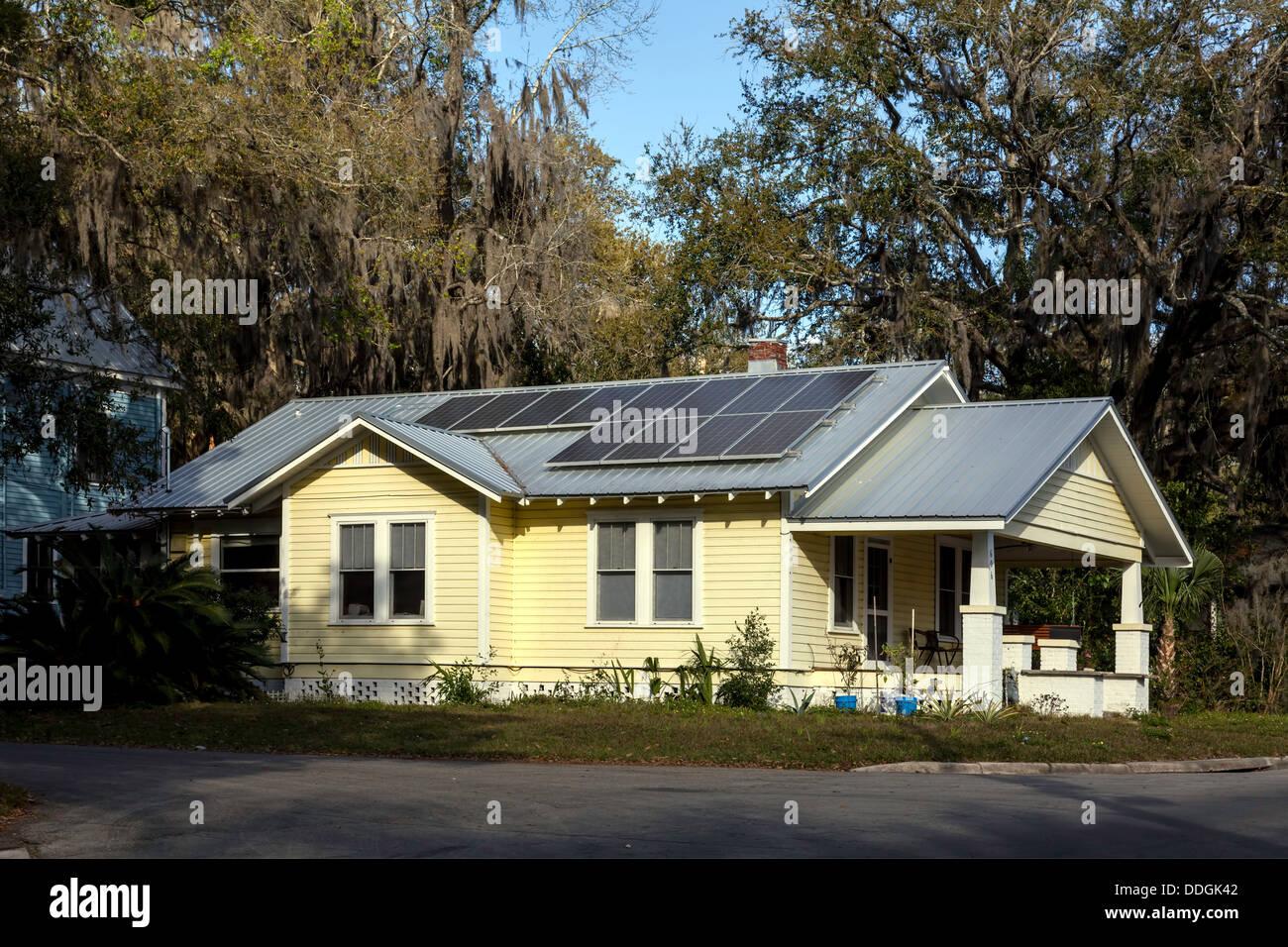 Bonito bungalow casa amarilla con renovaciones sostenible incluyendo los paneles solares montados en el techo. Imagen De Stock