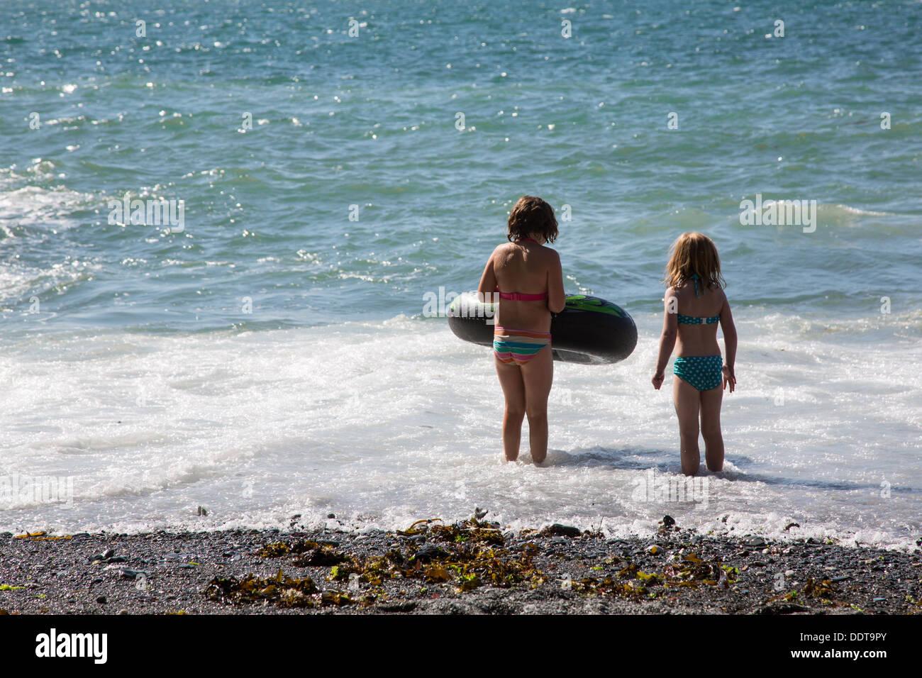 Dos niños jugando en el mar, en las playas de túneles, Ilfracombe, Devon Imagen De Stock