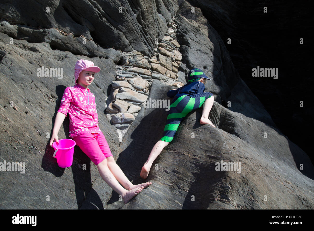 Dos niños jugando en las rocas en túneles Playas, Ilfracombe, Devon Imagen De Stock