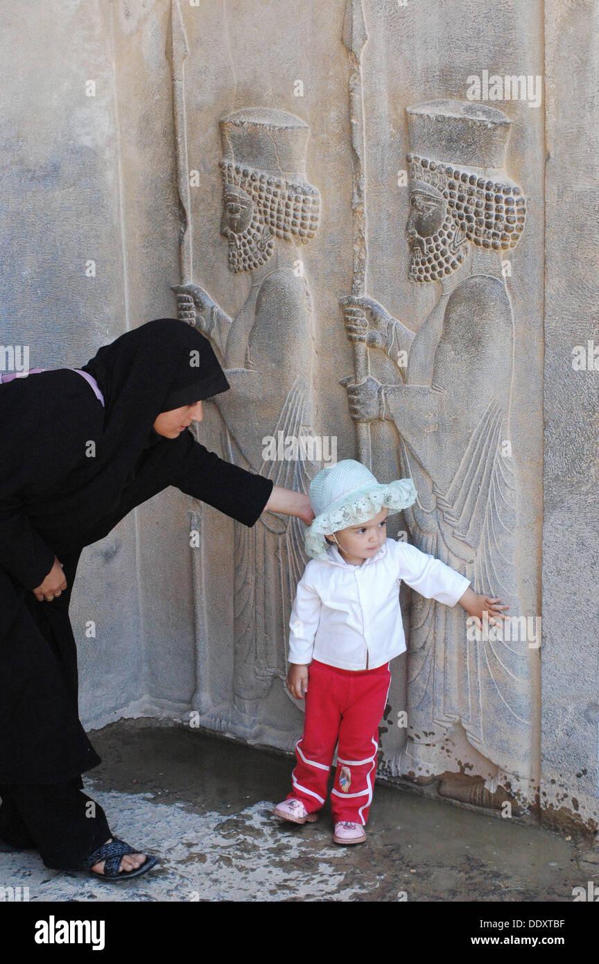 Los guerreros relieves y mujer en chador. Persépolis (Takht-e Jamshid). Fars. Irán Foto de stock