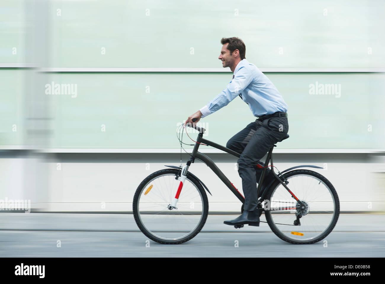Empresario montando bicicleta Foto de stock