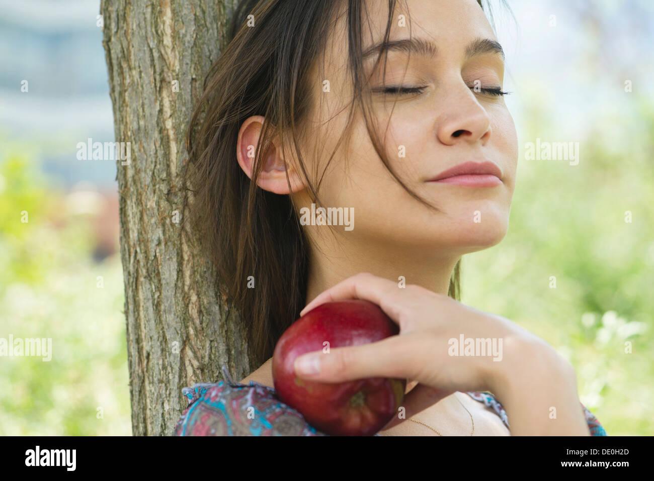 Mujer relajante al aire libre con los ojos cerrados, sosteniendo apple Imagen De Stock