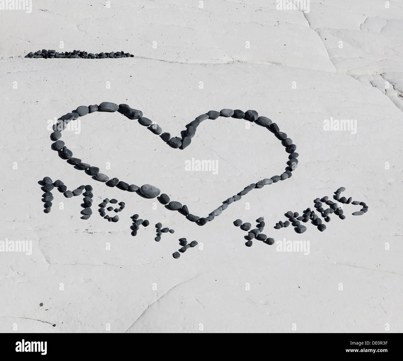 Merry X-Mas, hecha de piedras colocadas sobre una roca Imagen De Stock