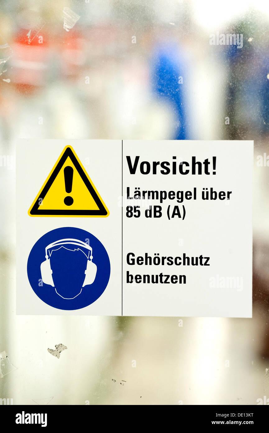 Señal de precaución en alemán, niveles de ruido superiores a 85 dB, utilizar protección auditiva, las directrices de la empresa para el uso de protección auditiva en Imagen De Stock