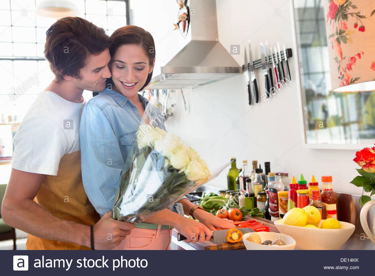 Hombre Mujer sorprendente en cocina con bouquet de flores Imagen De Stock