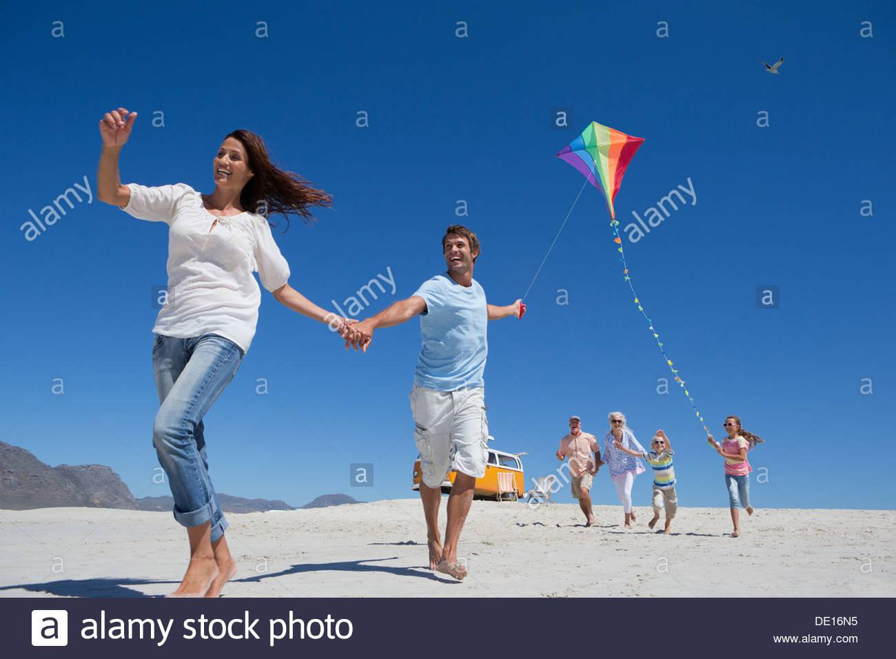 Multi-generación feliz familia con kite ejecutando en sunny beach Foto de stock
