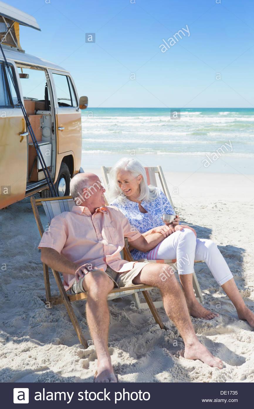 Felices parejas ancianas sentadas en sillas en Sunny Beach cerca de van Imagen De Stock