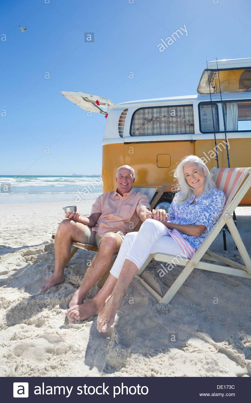 Retrato de pareja senior sonrientes sentados en sillas en Sunny Beach cerca de van Imagen De Stock