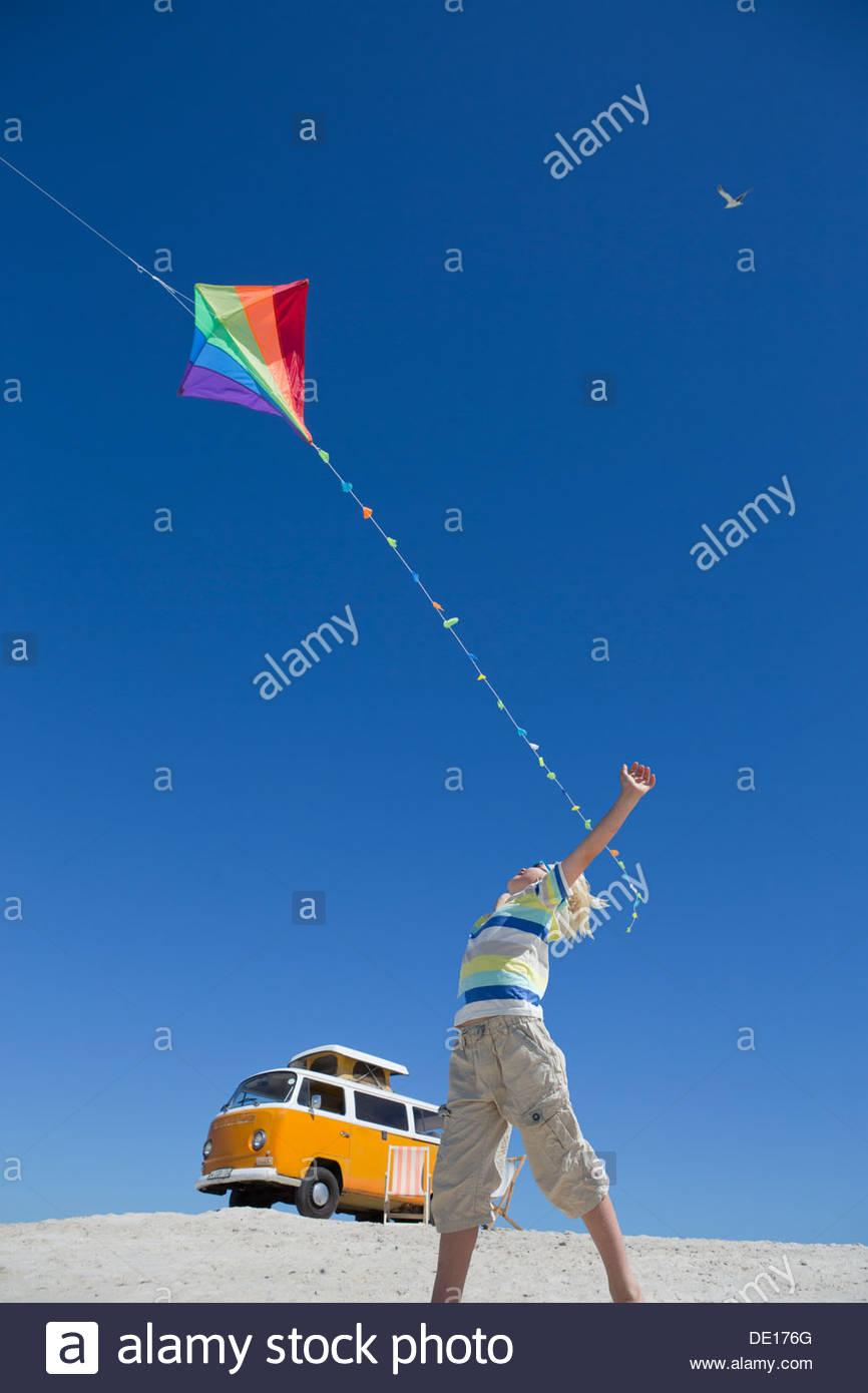 Niño volando cometa en sunny beach con van en segundo plano. Imagen De Stock