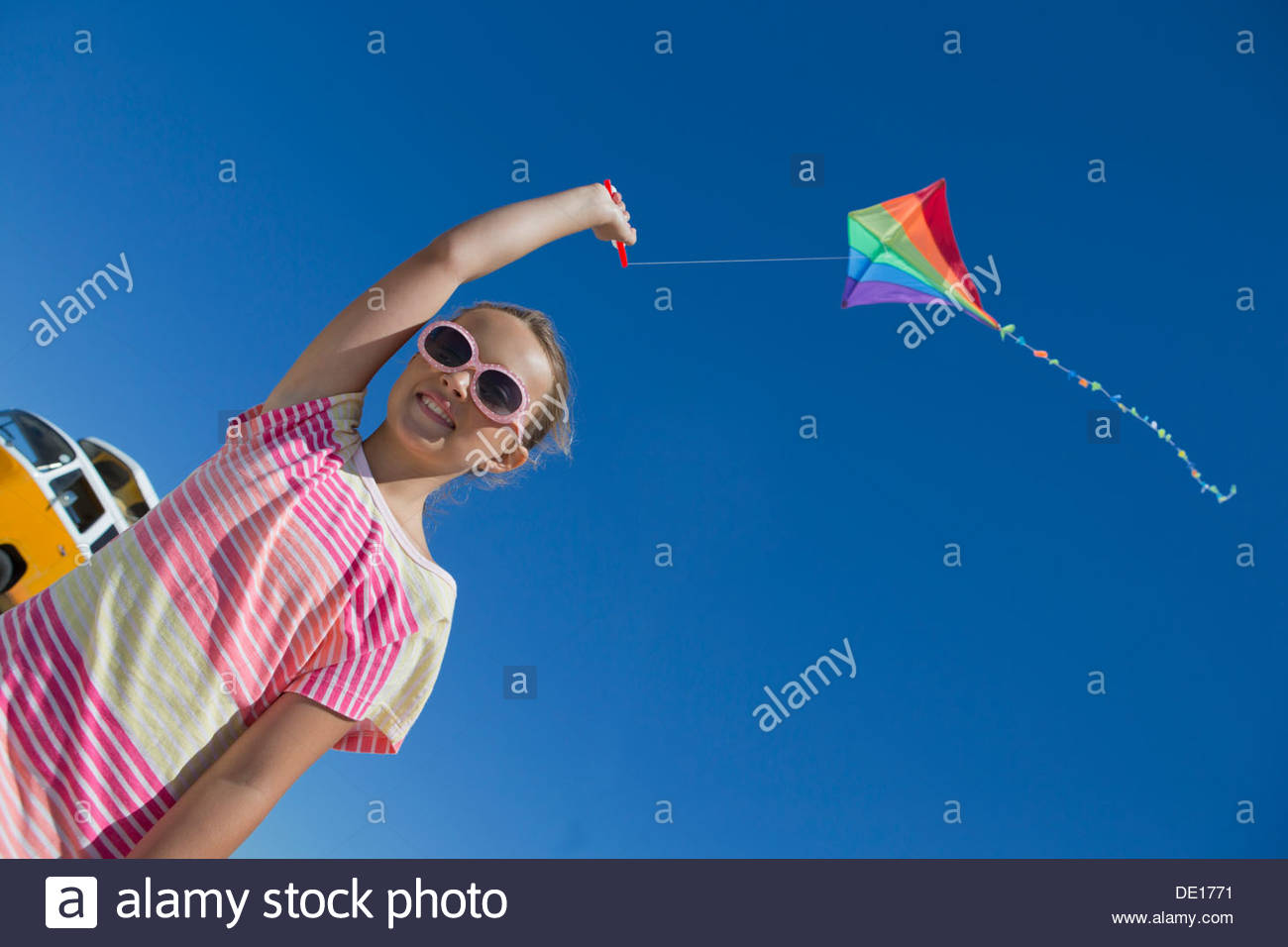 Chica volar cometa contra el cielo azul Imagen De Stock