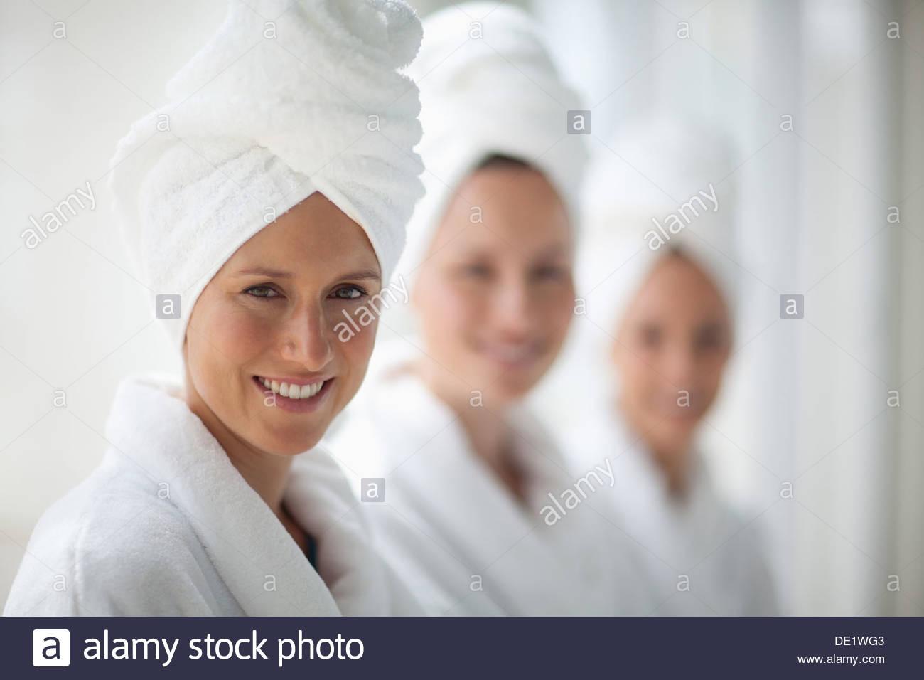 Retrato de mujer sonriente en batas y secador envuelto en toallas en spa Imagen De Stock