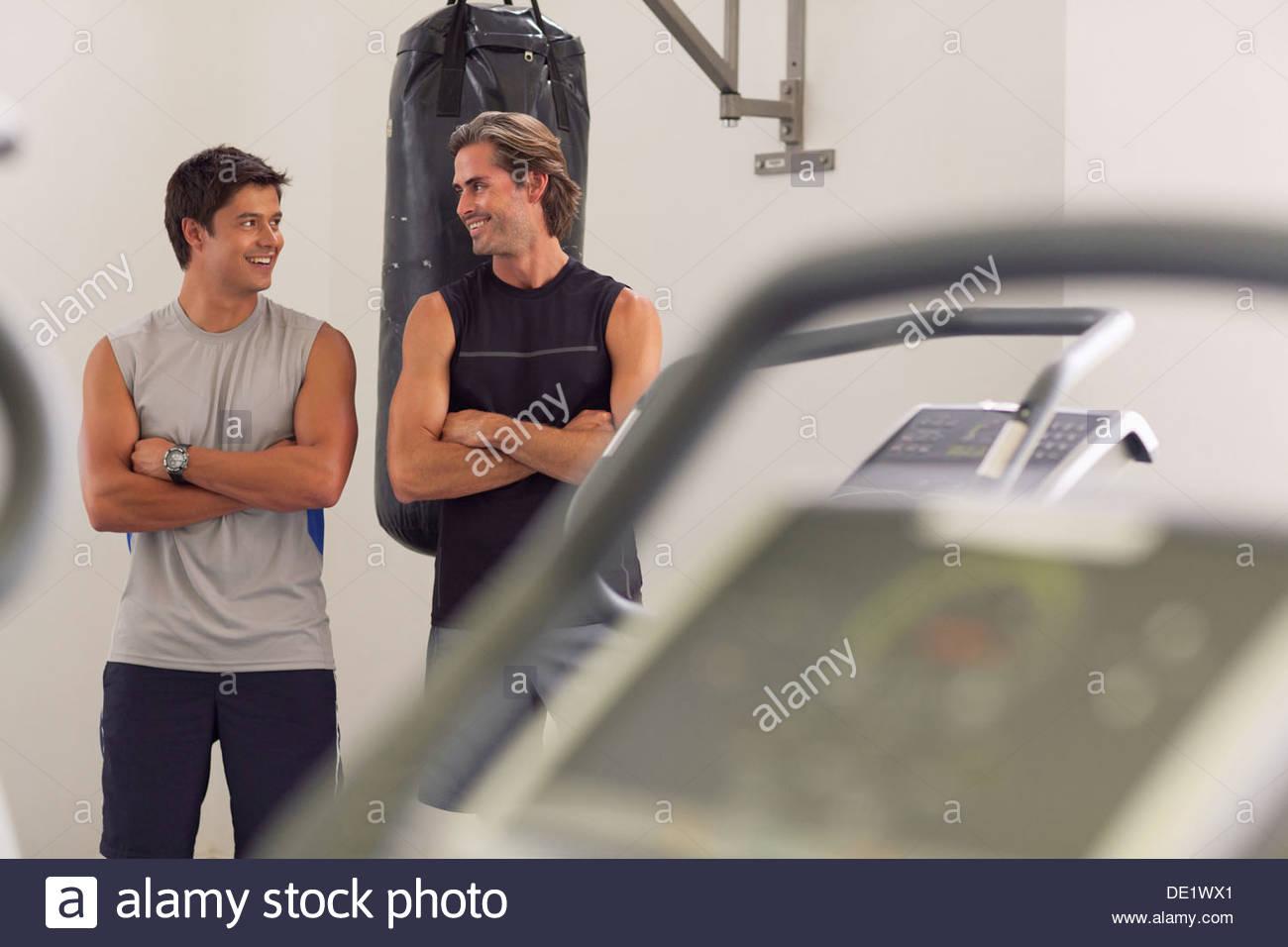 Retrato del hombre sonriente con los brazos cruzados delante de saco de boxeo Imagen De Stock