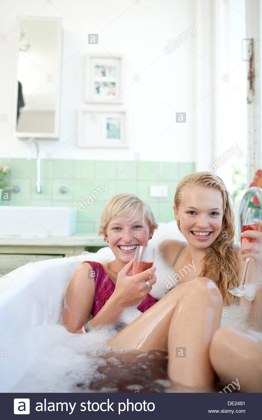 Las mujeres en vestir beber champán en la bañera. Imagen De Stock