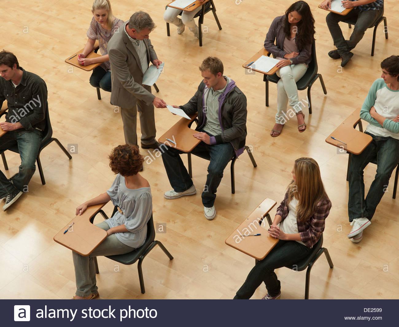 Profesor distribuir hoja de respuestas en el aula Imagen De Stock