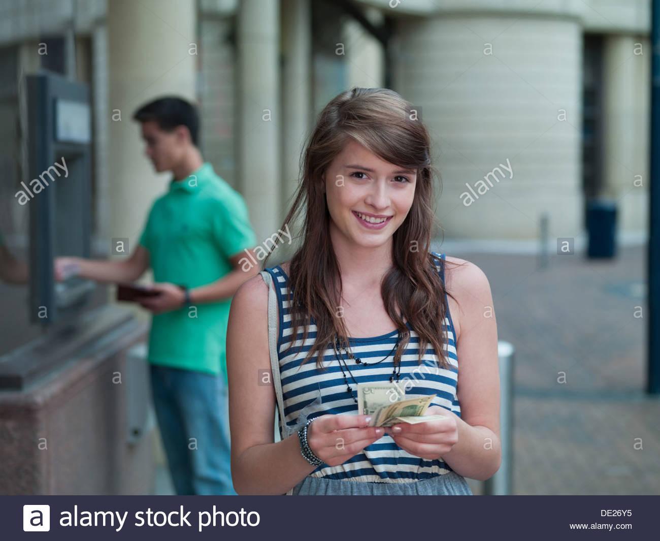 Niña alegre celebración dinero cerca del cajero automático Imagen De Stock