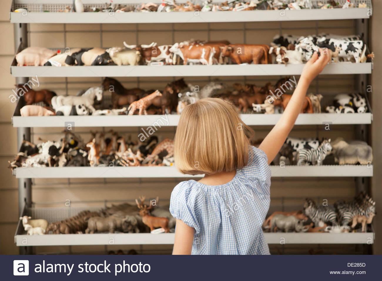 Niña alcanzando vaca de plástico en la tienda de juguetes Imagen De Stock