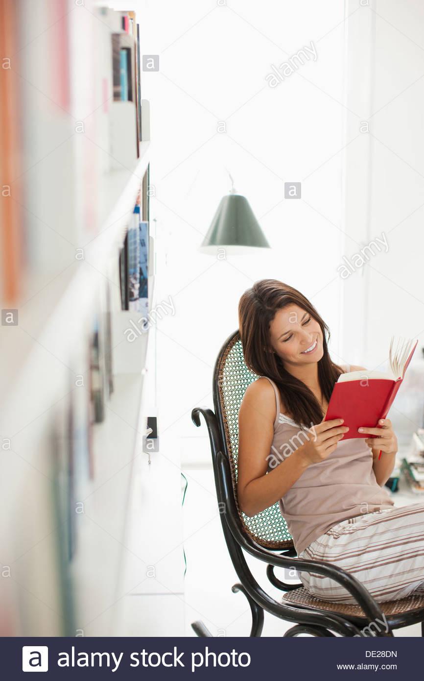 Mujer sonriente leyendo un libro Imagen De Stock
