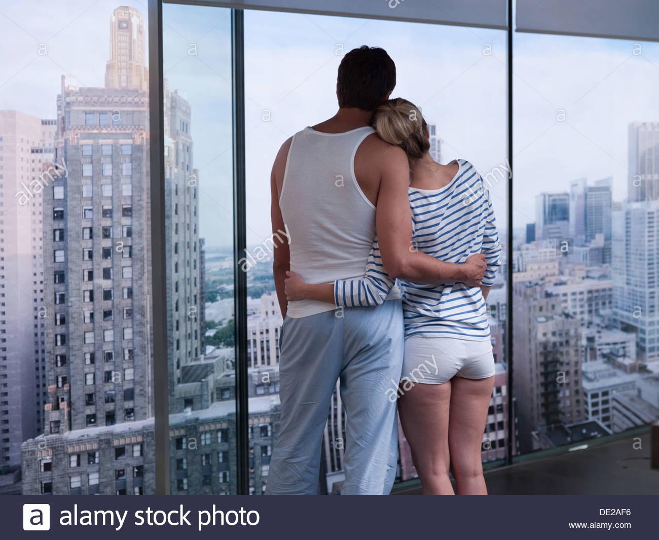 Pareja abrazarse y mirar hacia el exterior Imagen De Stock