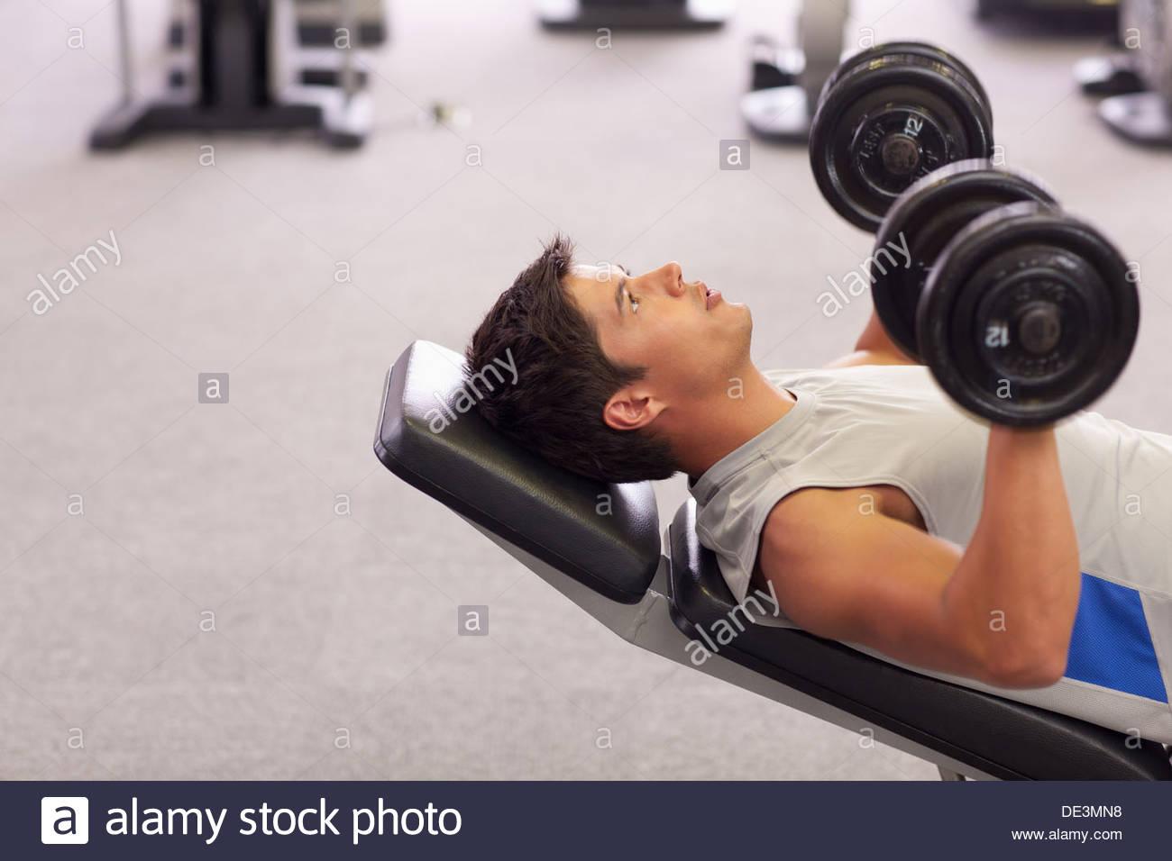 Hombre haciendo pendiente presiona el pecho con pesas en el gimnasio Imagen De Stock
