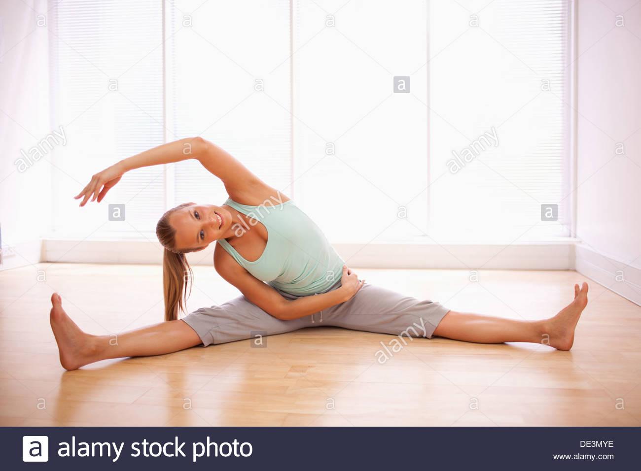 Retrato de mujer sonriente estiramientos con las piernas Imagen De Stock