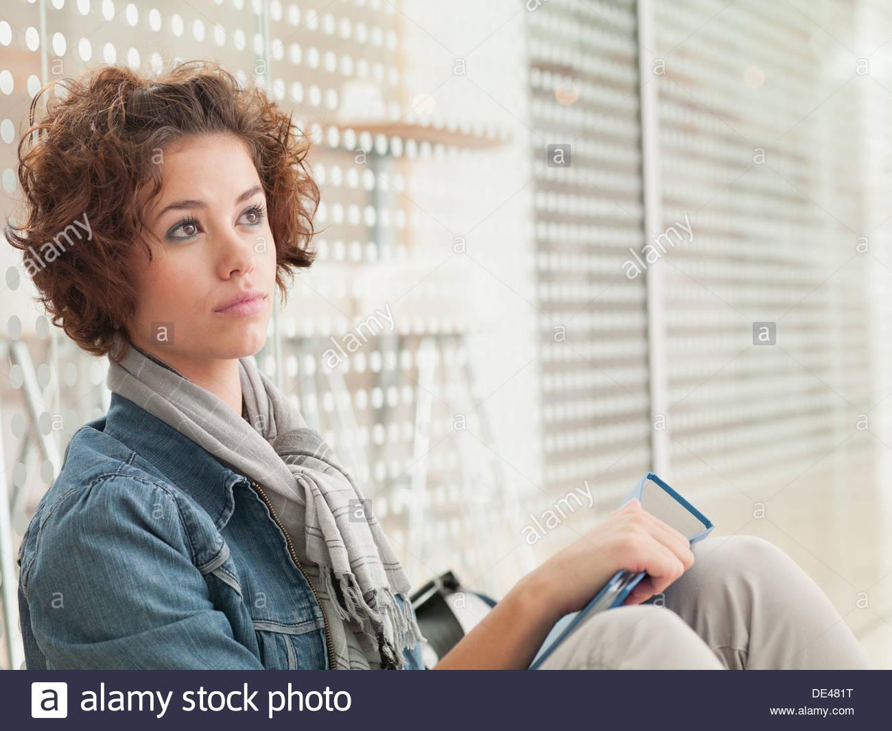 Mujer sosteniendo pensativo libro Imagen De Stock