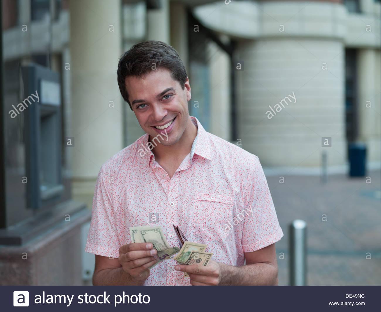 Hombre sonriendo contando dinero cerca del cajero automático Imagen De Stock