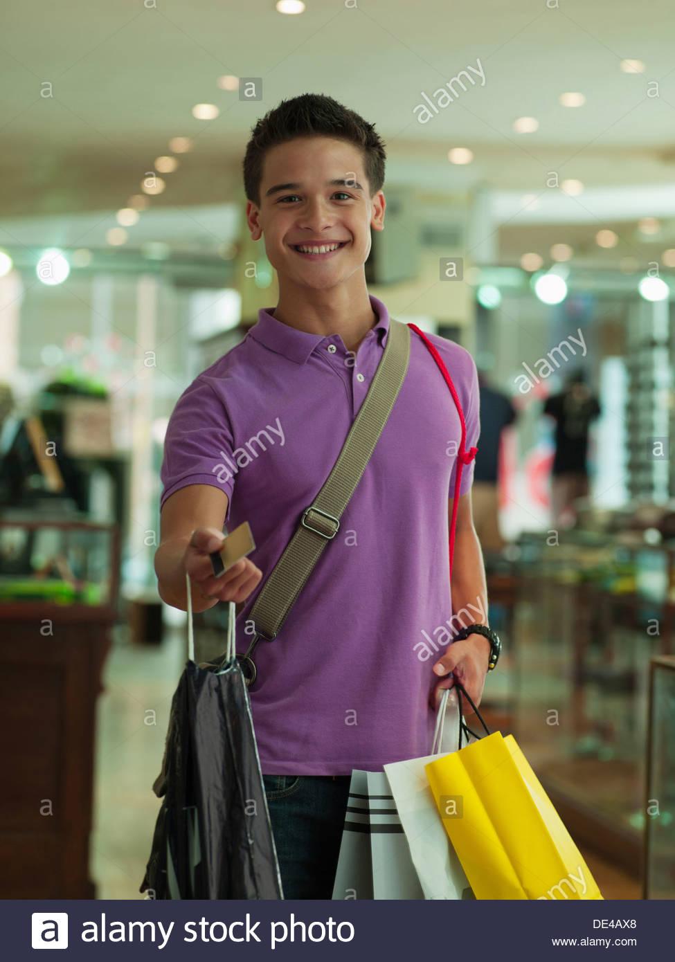 Hombre sonriente mostrar tarjeta de crédito con llevar bolsas de la compra en la tienda Imagen De Stock