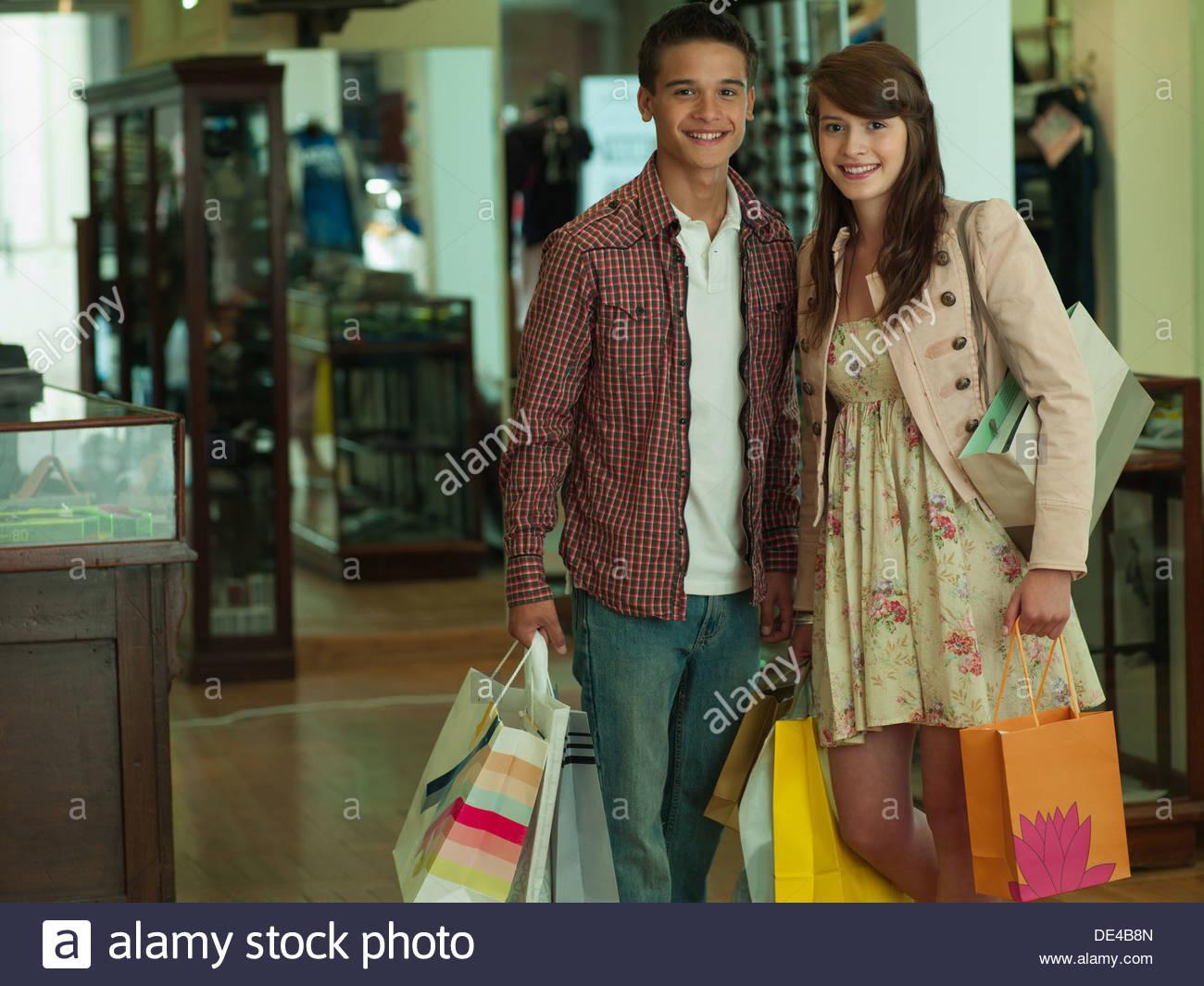 Pareja sonriente llevando bolsas de compras en la tienda de ropa Imagen De Stock
