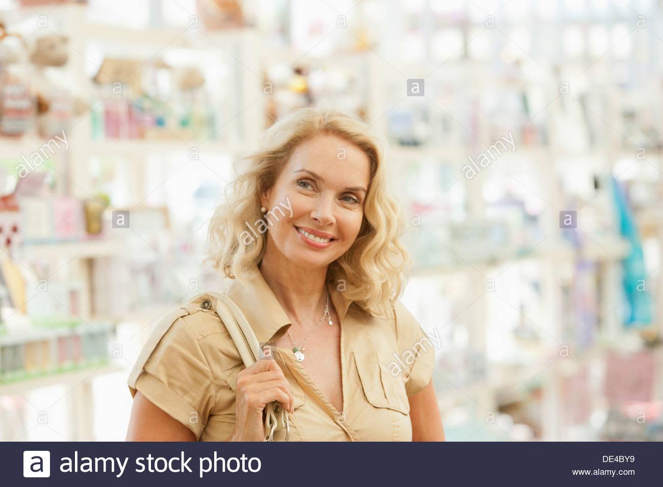 Mujer sonriente compras en tienda Imagen De Stock