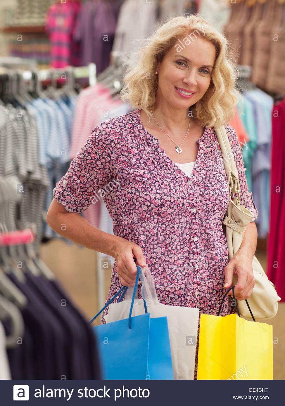 Mujer sonriente llevando bolsas de compras en la tienda de ropa Imagen De Stock