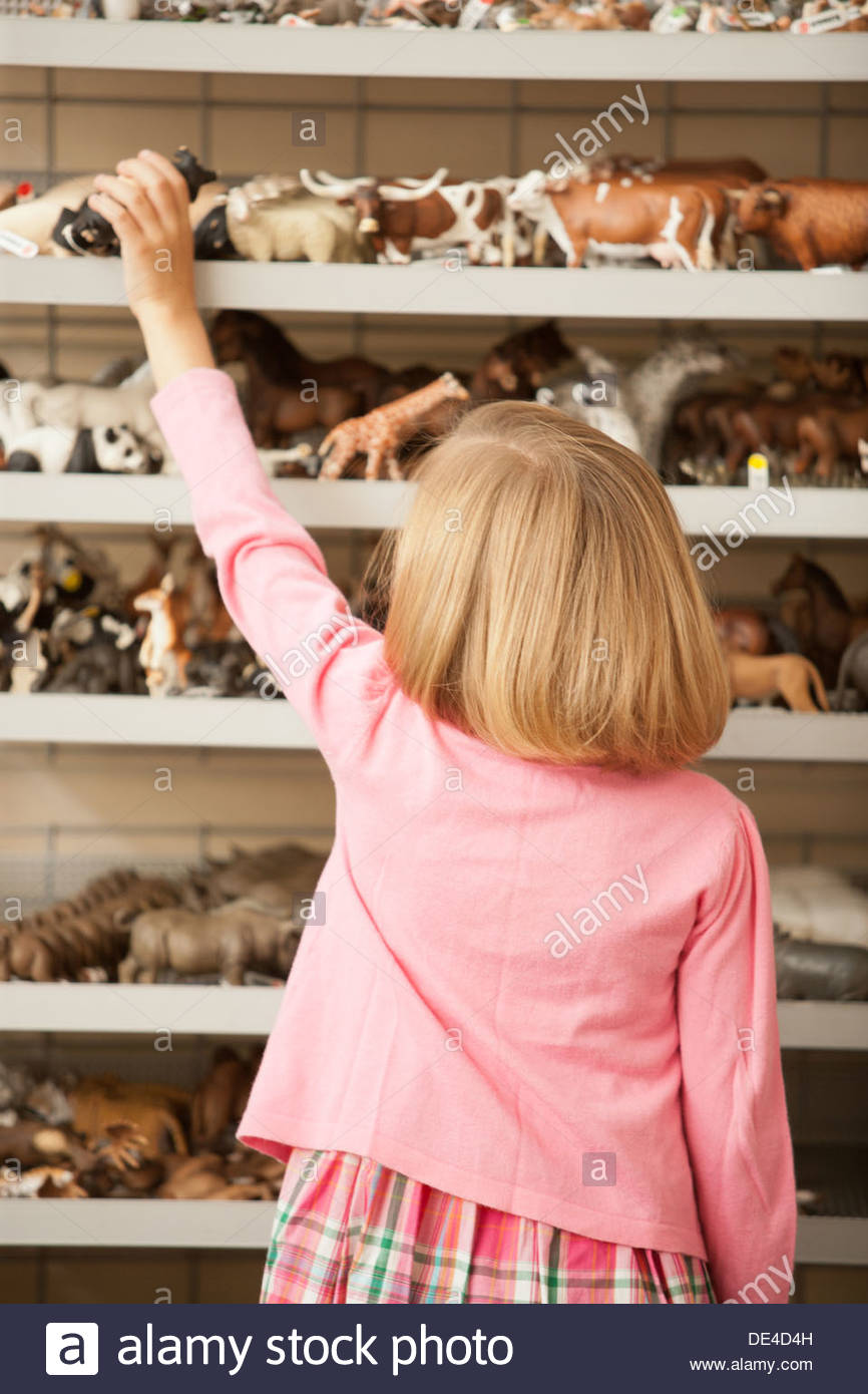 Niña alcanzando cerdo de plástico en la tienda de juguetes Imagen De Stock