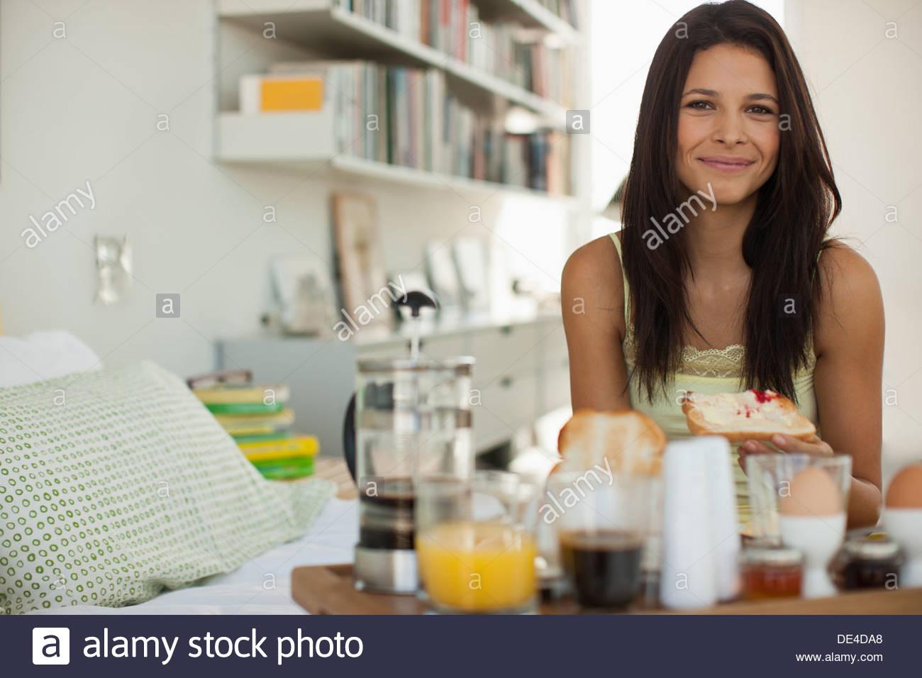 Mujer sonriente desayunando en la cama Imagen De Stock