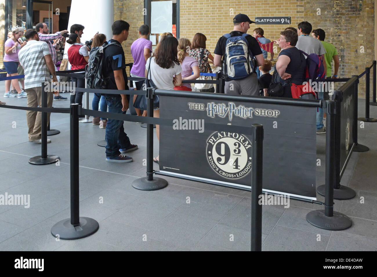 Fans haciendo cola para tener una foto tomada en la plataforma nueve y tres cuartos sign desde historia de Harry Potter en la estación Kings Cross Imagen De Stock