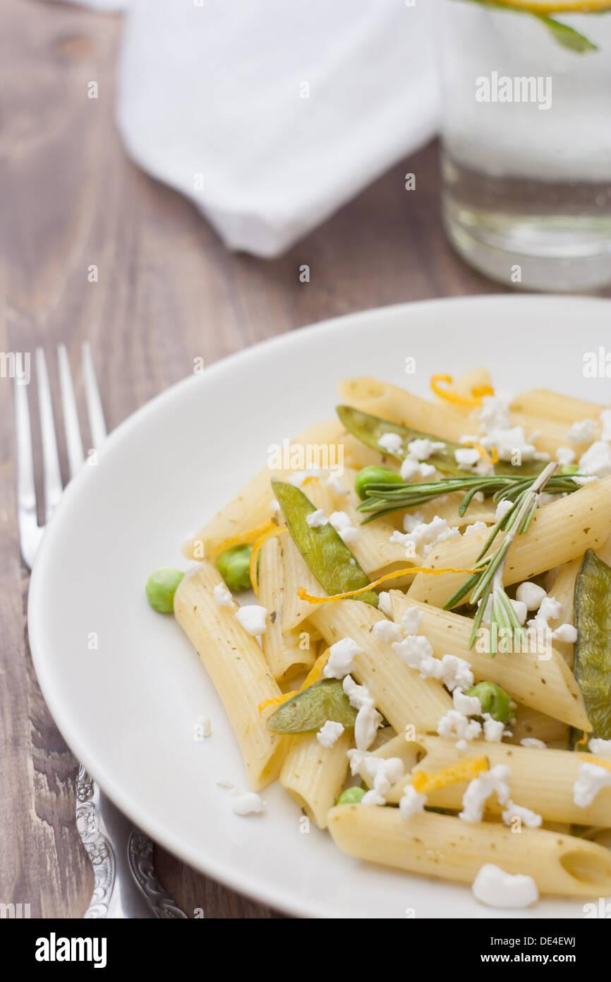 Deliciosa pasta vegetariana con guisantes y queso feta. Imagen De Stock