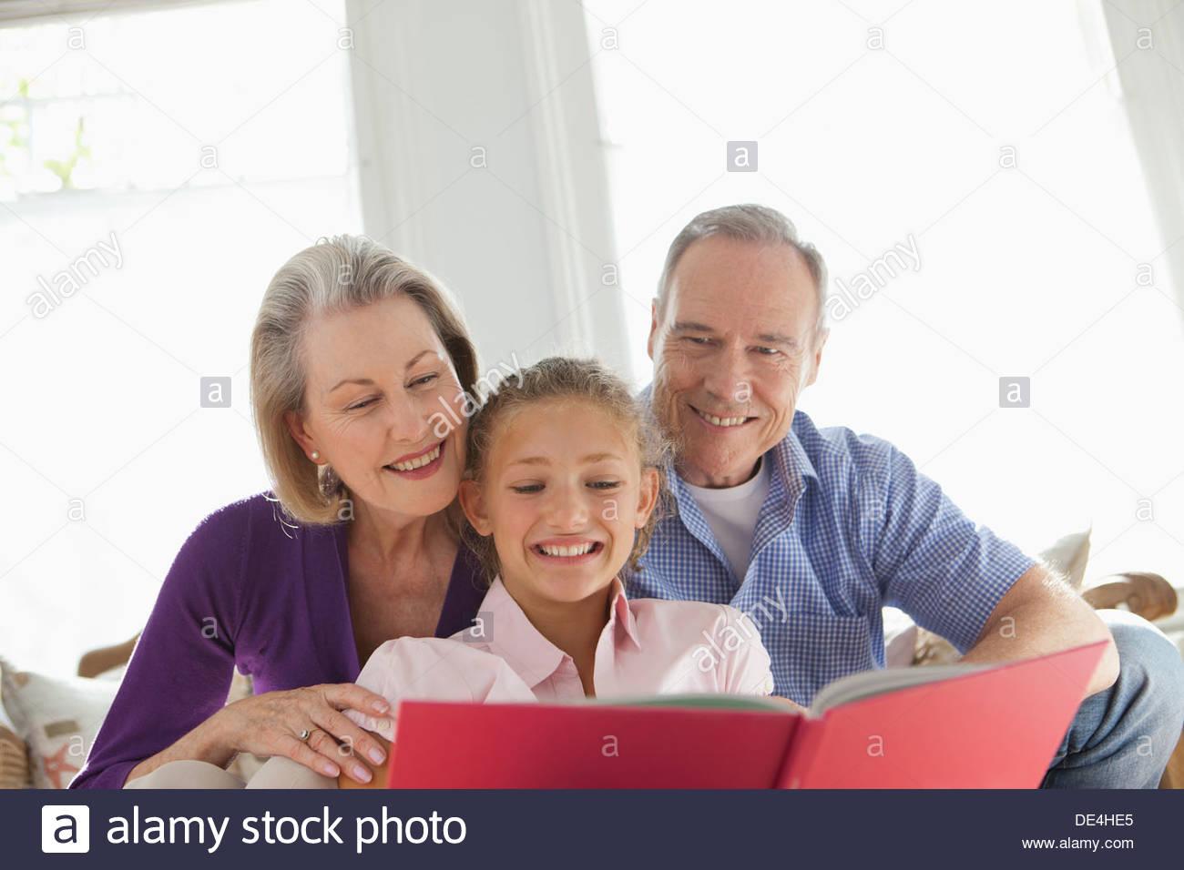Los abuelos sonrientes y nieta de lectura Imagen De Stock