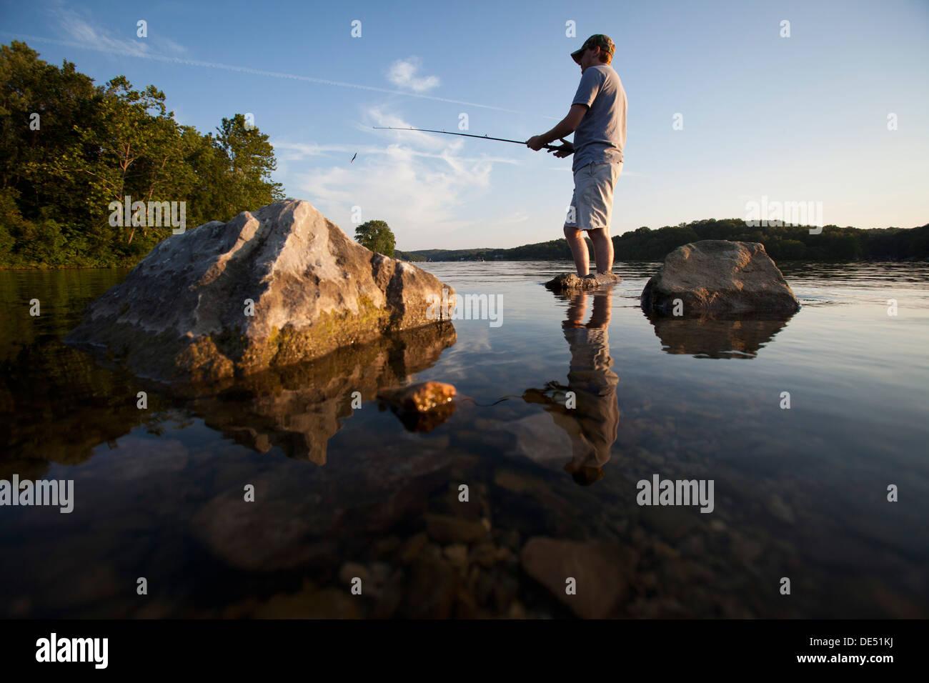 Un hombre arroja su línea mientras la pesca en el lago Windsor en Bella Vista, Arkansas. Imagen De Stock
