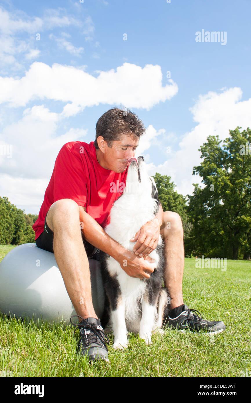 Un perro da su propietario afectuosos besos mientras toma un descanso en su rutina de ejercicio. Imagen De Stock