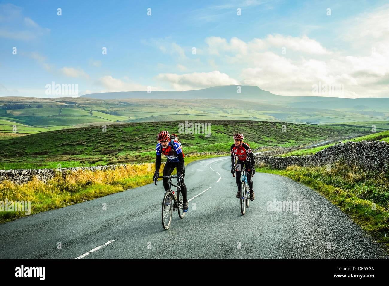 Los ciclistas en Ribblesdale en Yorkshire Dales National Park con Pen-y-Ghent detrás Imagen De Stock
