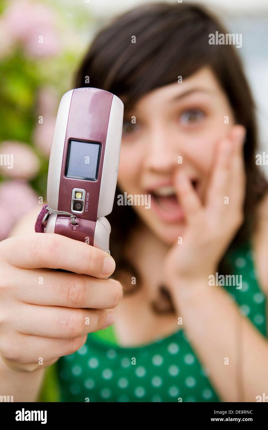 Adolescente de 17 años, leyendo mensajes en telefono movil.MR: 50203. Imagen De Stock