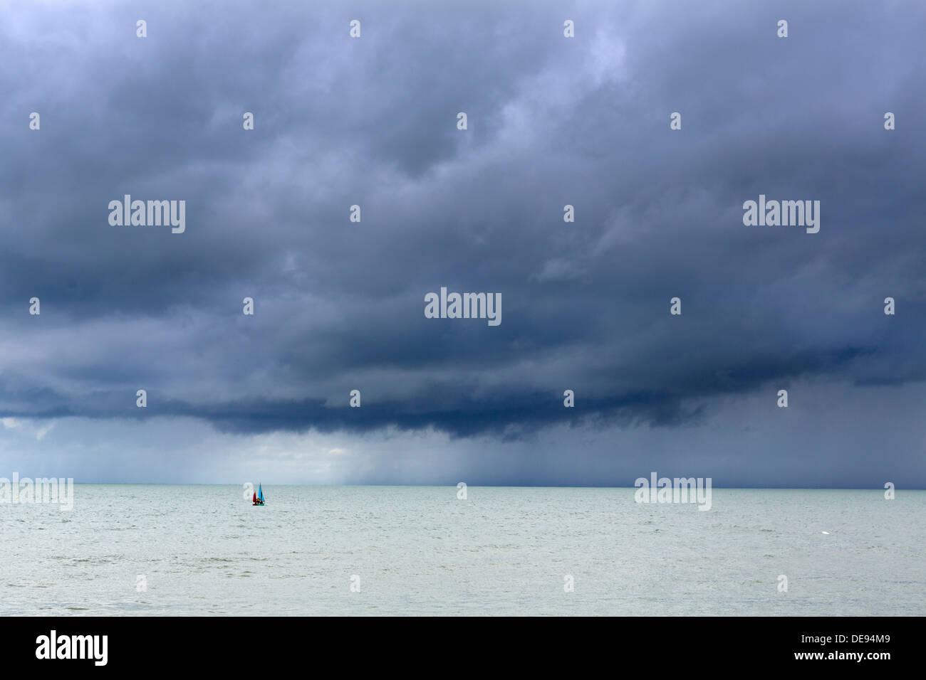 Pequeño bote navegando hacia una tormenta en la costa de la aldea costera de Aberaeron, Ceredigion, Gales, Imagen De Stock
