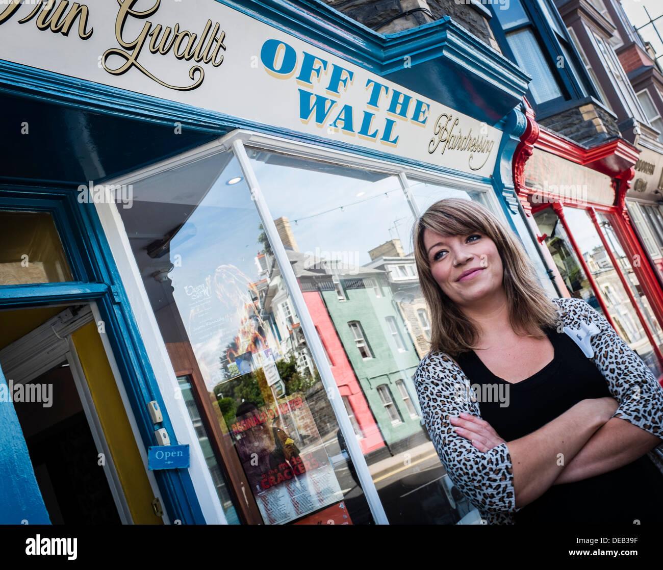 Michelle Kimberley Lewis, autónomo propietario de fuera del muro peluquería, Northgate St, Aberystwyth, de pie fuera de su tienda Imagen De Stock