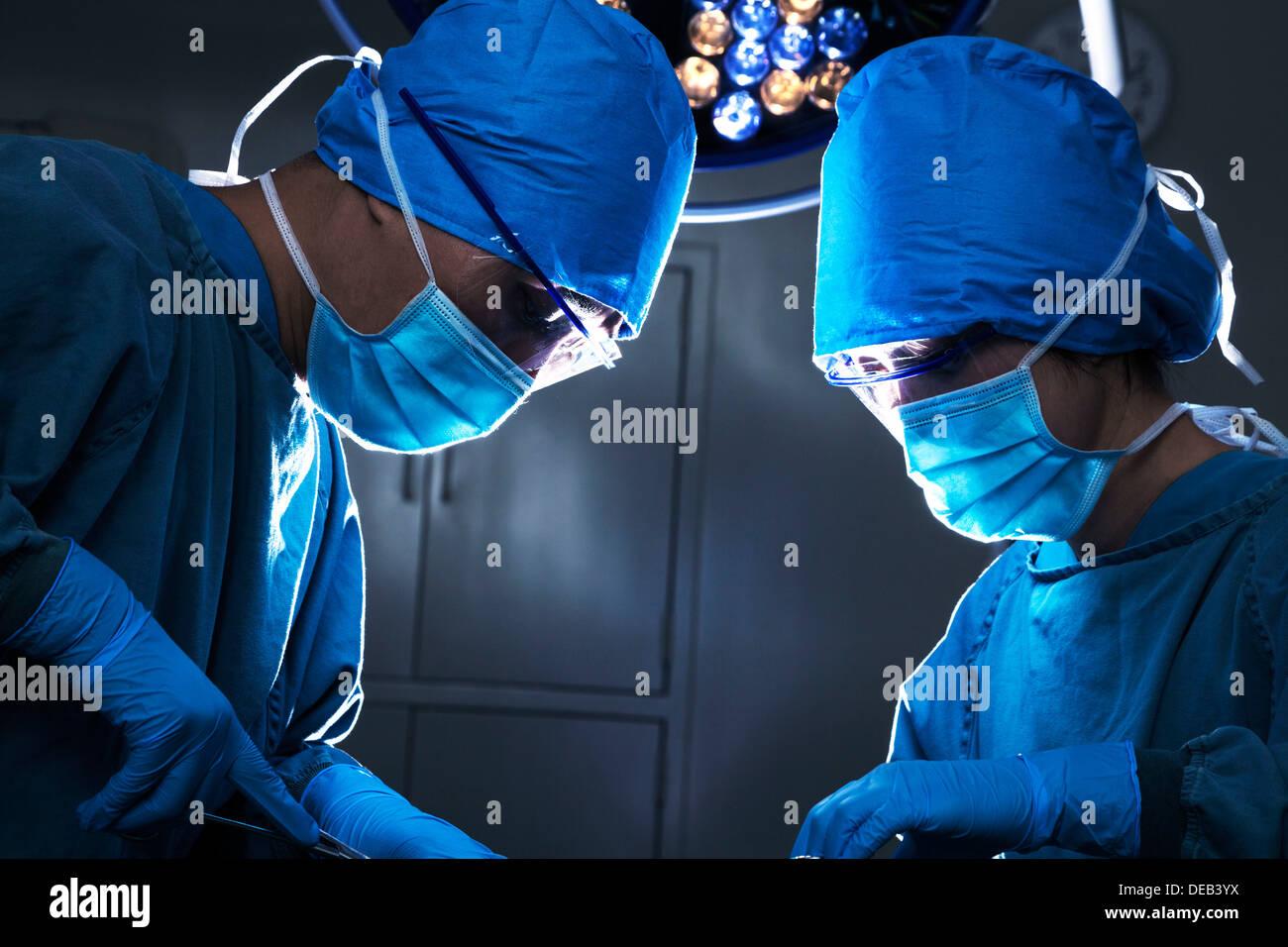 Dos cirujanos mirando hacia abajo, el trabajo y concentrarse en la mesa de operaciones Foto de stock