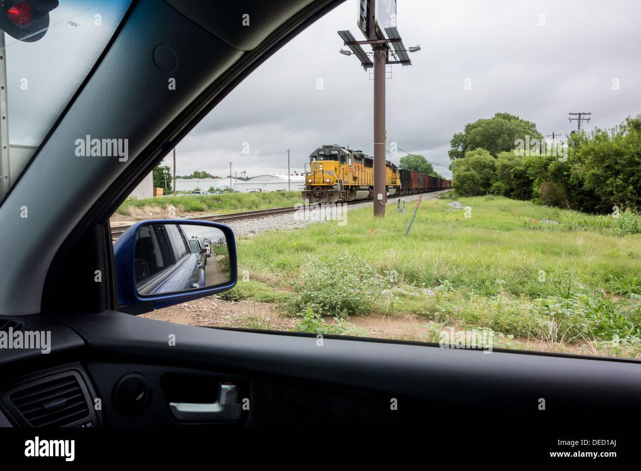 Desde el interior de un automóvil, un tren de mercancías se acercan vistos a través de la ventana. Imagen De Stock