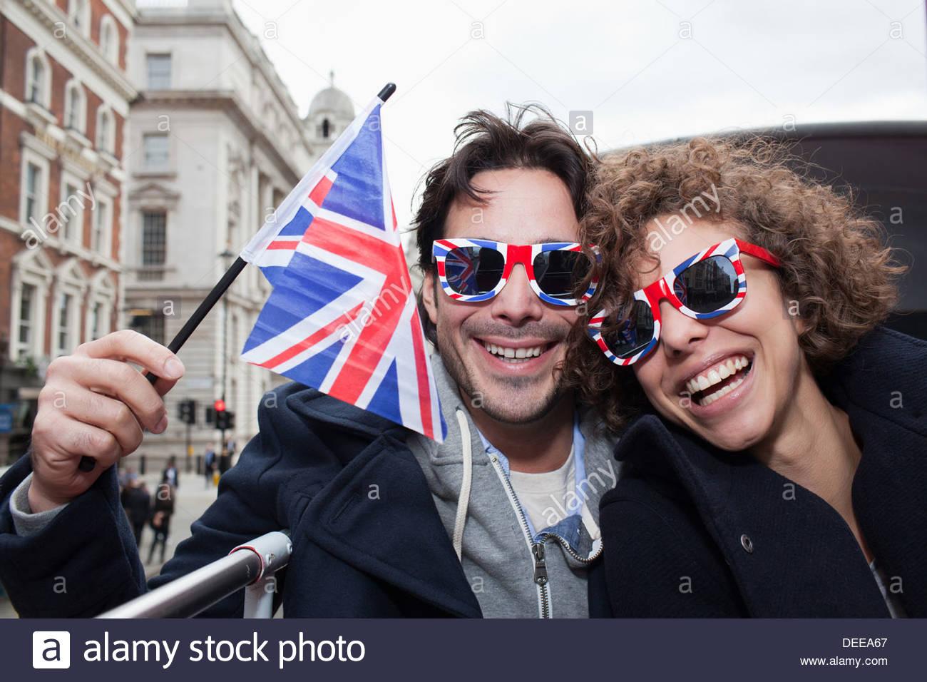 Retrato de una exuberante pareja con bandera británica y gafas de sol cabalgando double decker bus Imagen De Stock