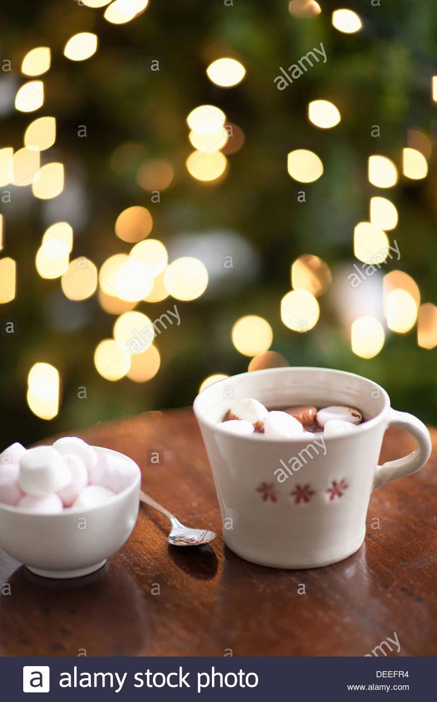 Taza de chocolate caliente, árbol de Navidad en segundo plano. Imagen De Stock